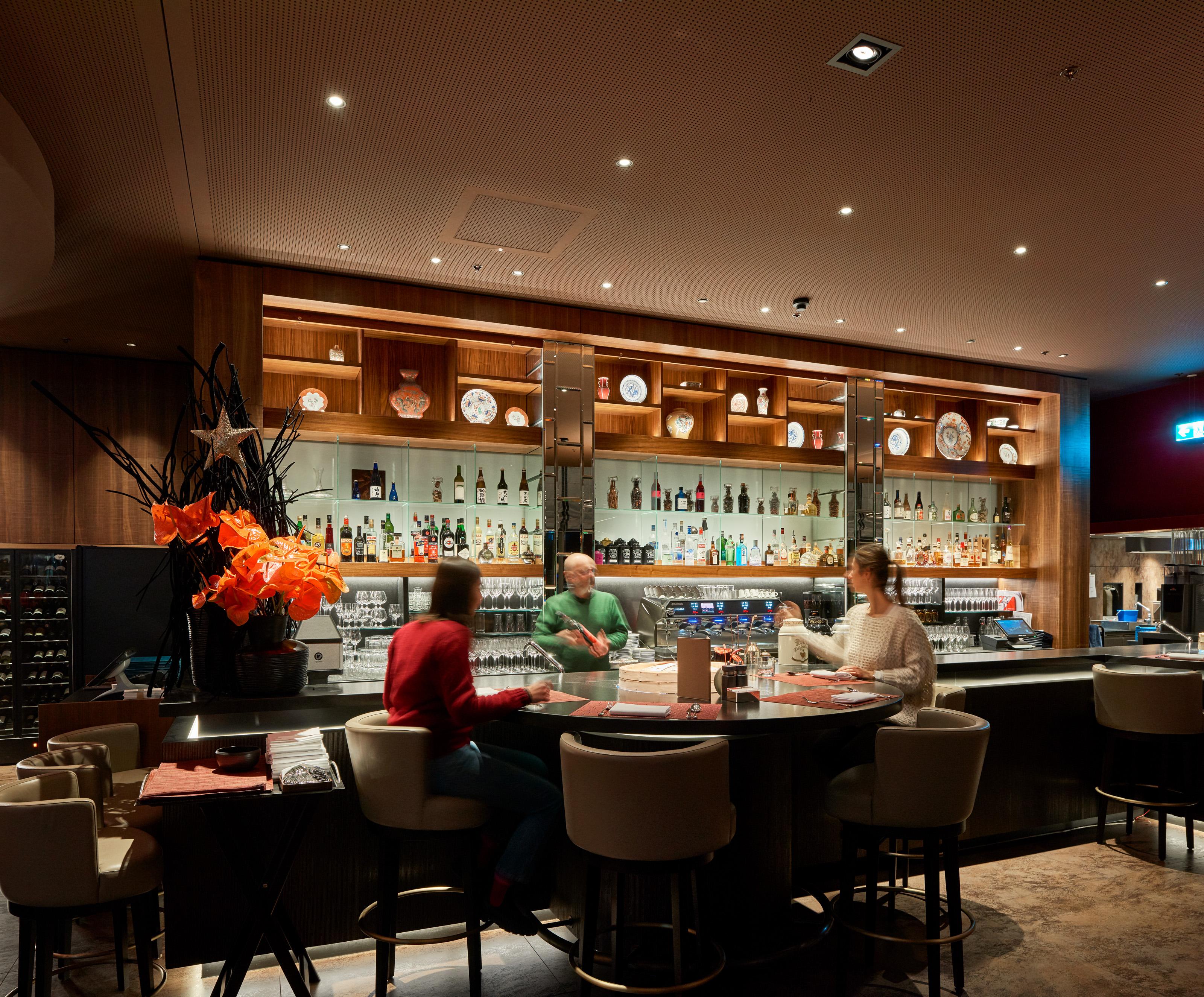 Gäste sitzen um eine runde Bar, das Lichtkonzept schafft ein nächtlches Abiente